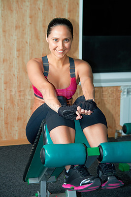 Buy stock photo Portrait of an attractive young woman doing leg curls in the gym