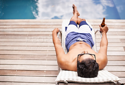 Buy stock photo Rear view shot of a young man lounging be the pool with a beer