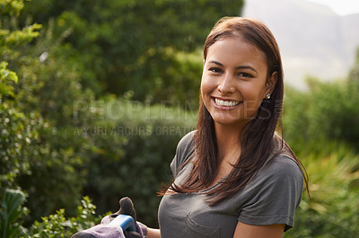 Buy stock photo Shot of an attractive young woman watering her garden