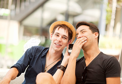 Buy stock photo Shot of two friends sharing a phone call outdoors