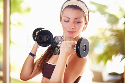 Buy stock photo Shot of an attractive young woman working out with dumbells