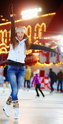 Buy stock photo Shot of a beautiful young woman skating on an ice rink at night