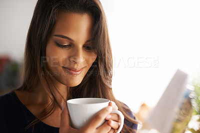Buy stock photo Shot of an attractive young woman drinking a coffee at home