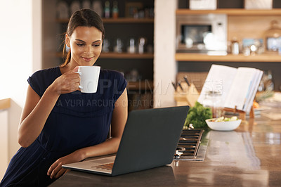 Buy stock photo Shot of an attractive young woman using her laptop while enjoying a cup of coffee