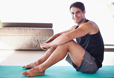 Buy stock photo A portrait of a happy young man sitting on an exercise mat at home
