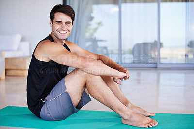 Buy stock photo A portrait of a happy young man stretching on an exercise mat at home