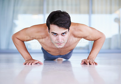 Buy stock photo A portrait of a focused young man doing strength exercises at home