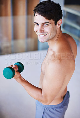 Buy stock photo A portrait of a happy young man lifting dumbbells at home