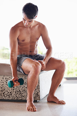 Buy stock photo A muscular young man sitting and lifting dumbbells at home