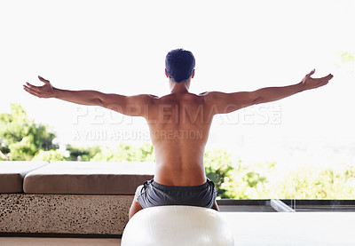 Buy stock photo A rear view shot of a muscular young man stretching while sitting on an exercise ball