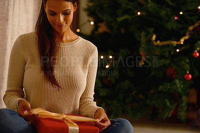 Buy stock photo Shot of  a beautiful young woman sitting indoors wrapping a gift