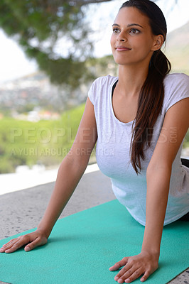 Buy stock photo Shot of a beautiful young woman doing yoga on a mat