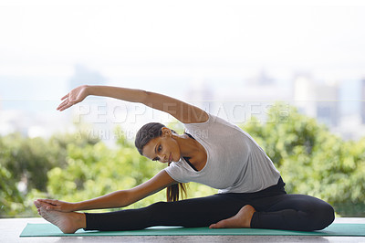 Buy stock photo An attractive young woman stretching on a yoga mat