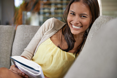 Buy stock photo Portrait of an attractive young woman reading a book while sitting on a couch