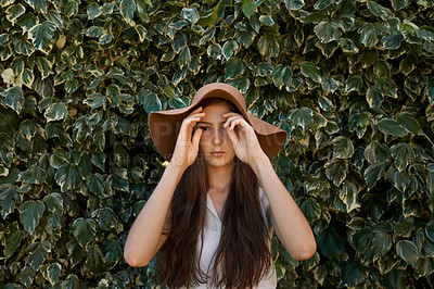 Buy stock photo Cropped shot of a pretty teenage girl standing in front of a large hedge