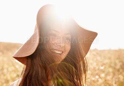 Buy stock photo Shot of an attractive teenage girl in a field with the sun behind her