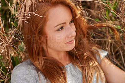 Buy stock photo Shot of a pretty teenage looking thoughtful while sitting in a field