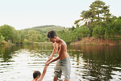 Buy stock photo Shot of a teenage boy helping his friend out of the water