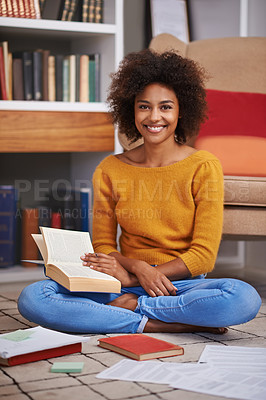 Buy stock photo Portrait of an attractive young woman sitting on the floor while studying