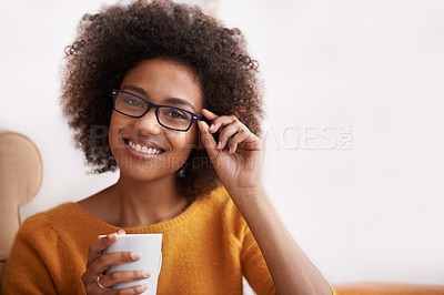 Buy stock photo Portrait of an attractive young woman smiling while holding a cup of coffee