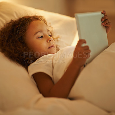 Buy stock photo A young girl lying on her bed while using a digital tablet