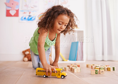 Buy stock photo Shot of a little girl playing with a toy truck and building blocks