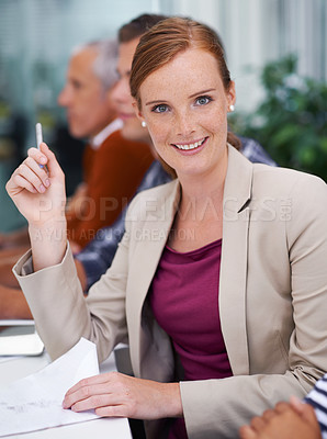 Buy stock photo Shot of a young businesswoman sitting in a board meeting
