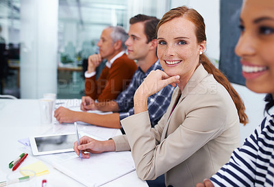 Buy stock photo Shot of a businesswoman smiling at the camera during a meeting with her colleagues