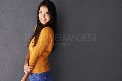 Buy stock photo Shot of a young woman standing against a dark background
