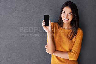 Buy stock photo An attractive young woman holding up a mobile phone while standing against a gray wall