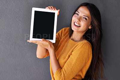 Buy stock photo Portrait of an attractive young woman holding up a digital tablet with a blank screen