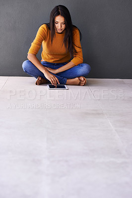 Buy stock photo Shot of an attractive young woman sitting on the floor with her digital tablet
