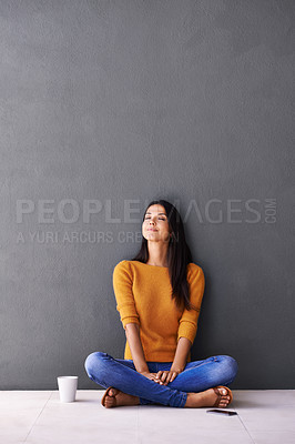 Buy stock photo Shot of an attractive young woman sitting on the floor with her mobile phone and a cup of coffee