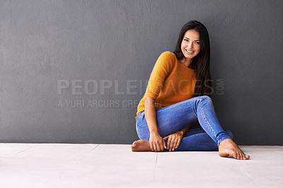 Buy stock photo Portrait of an attractive young woman sitting against a gray wall