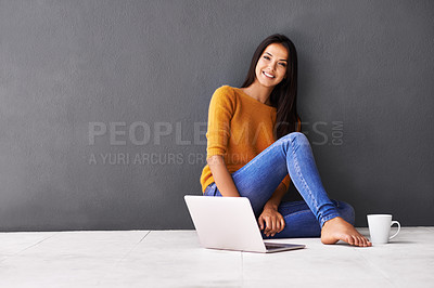Buy stock photo Portrait of an attractive young woman sitting on the floor with a laptop