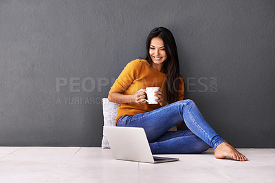 Buy stock photo An attractive young woman drinking coffee while sitting on the floor with a laptop