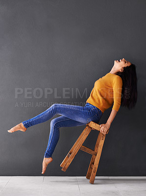 Buy stock photo Shot of a happy young woman laughing while leaning back on a stool