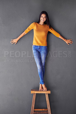 Buy stock photo Portrait of an attractive young woman standing on a stool with her arms outstretched