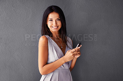 Buy stock photo Studio shot of an attractive young woman using her cellphone