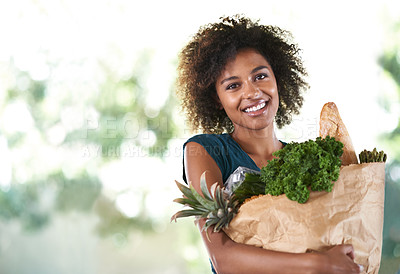 Buy stock photo Young girl smiling while holding her groceries - isolated