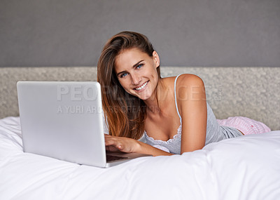 Buy stock photo Shot of an attractive young woman using her laptop while lying on the bed