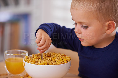 Buy stock photo Cropped shot of a young boy eating breakfast at home