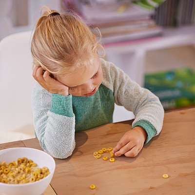 Buy stock photo Shot of a little girl looking sad while eating breakfast at home