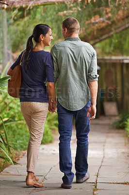 Buy stock photo Rear view shot of a young couple taking a walk in the garden