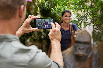 Buy stock photo A young man taking a photograph of his girlfriend at the zoo