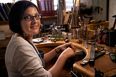 Buy stock photo A happy young woman working at a woodworking bench