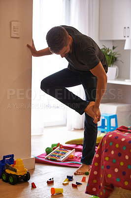Buy stock photo Shot of a man grabbing his foot in pain after standing on a child's toy