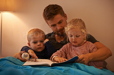 Buy stock photo A father reading a bedtime story to his kids