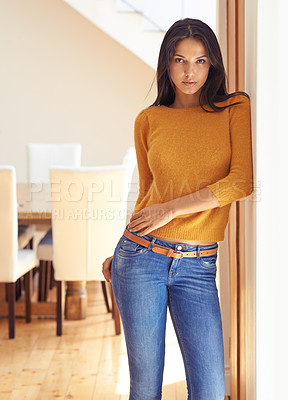Buy stock photo Gorgeous young woman in jeans leaning against a wall