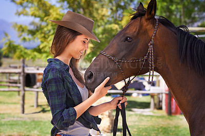 Buy stock photo Shot of a young cowgirl standing outside with her horse